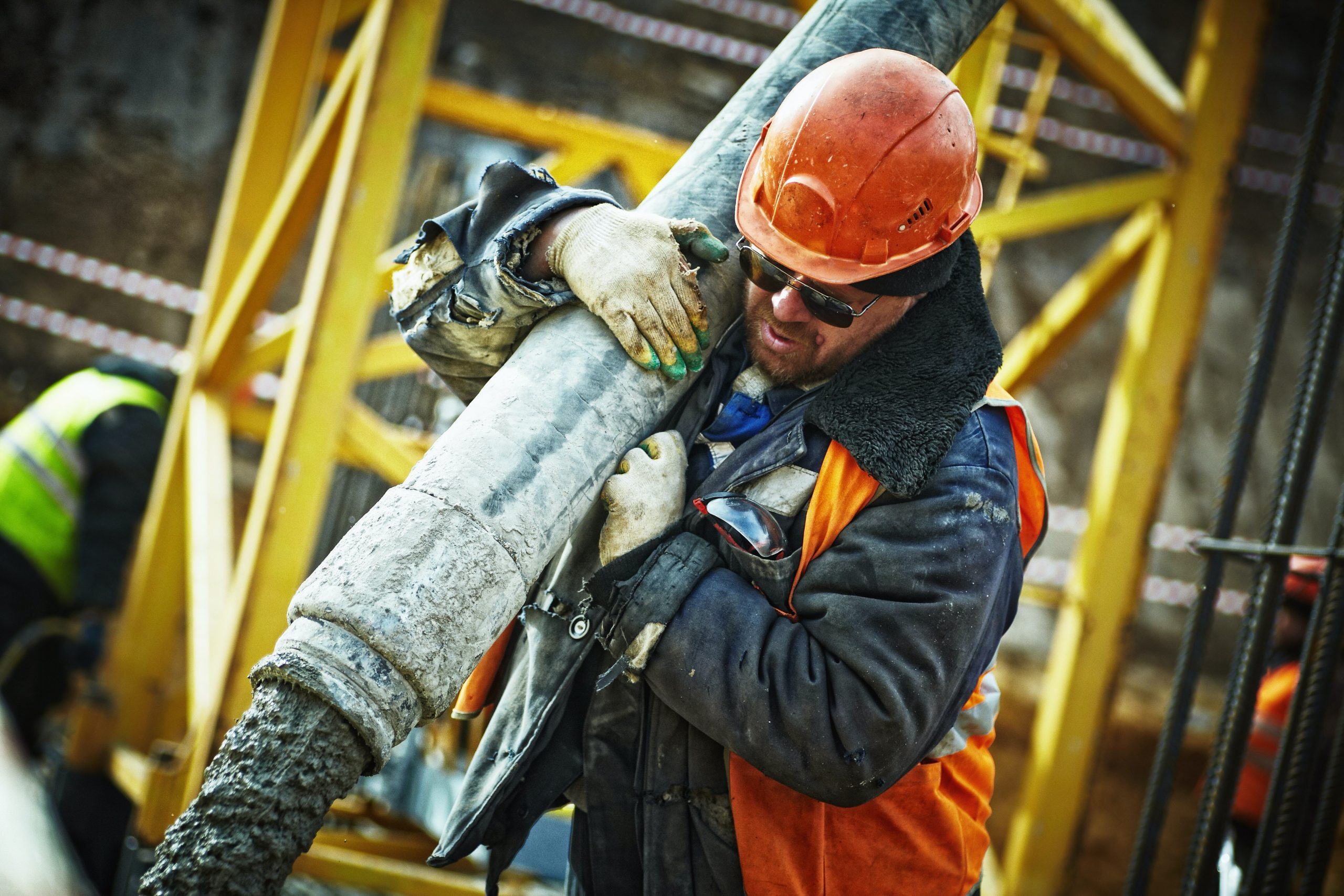 worker-holding-heavy-concrete-pipe